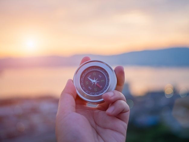Bussola della holding della mano con la priorità bassa del cielo di tramonto e della montagna. Foto Premium