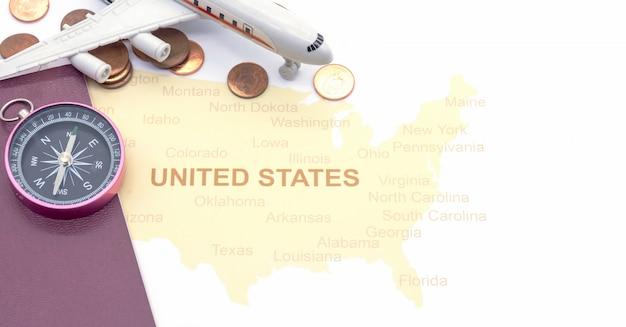 Bussola e monete del passaporto su una mappa americana. concetto di viaggio d'affari Foto Premium