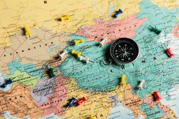Bussola magnetica e puntine sulla mappa. Foto Premium
