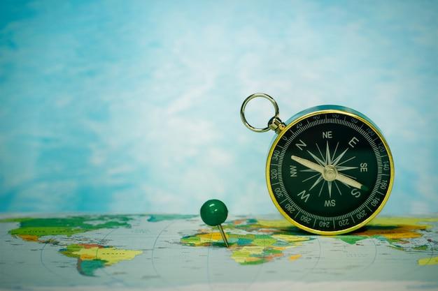 Bussola magnetica sulla mappa del mondo, concetto di viaggio e destinazione, macro viaggio Foto Premium