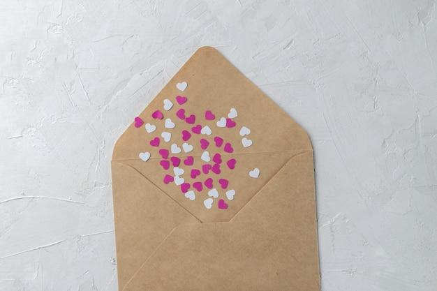 Busta artigianale con cuori di carta rosa e bianca Foto Premium