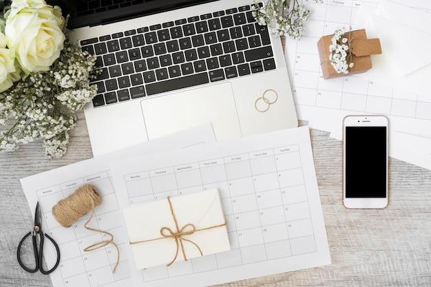 Busta; calendario; il computer portatile; fiori; smart phone; rocchetto; forbice e quaderno a spirale sulla scrivania in legno Foto Gratuite