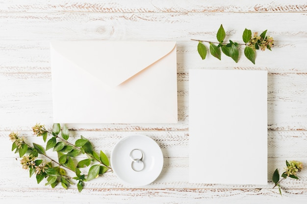 Busta chiusa; carta; ramoscello di fiori e fedi nuziali sul piatto sopra la scrivania bianca Foto Gratuite