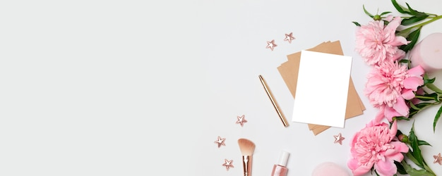 Busta kraft con un foglio di carta bianca, fiori di peonie, candele rosa Foto Premium