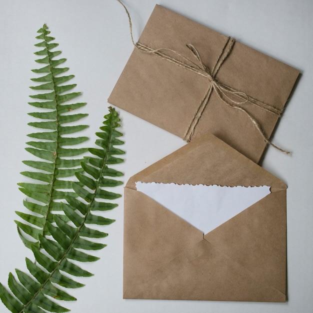 Buste artigianali beige, carta bianca vuota nota e foglie verdi tropicali. Foto Premium