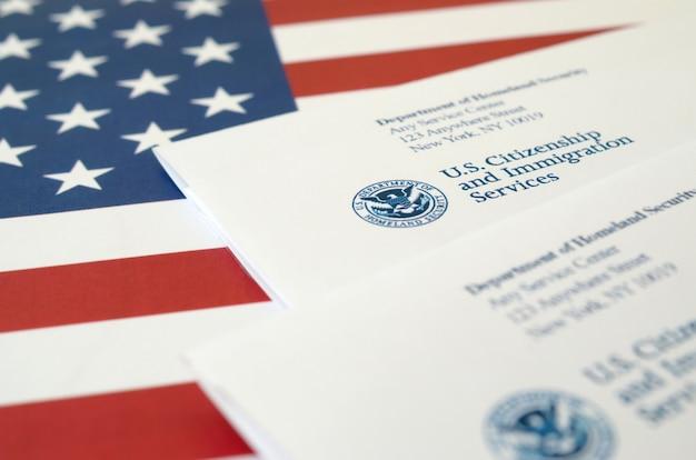 Buste con lettera dell'uscis sulla bandiera degli stati uniti del dipartimento della sicurezza interna Foto Premium