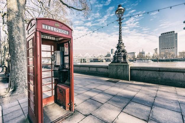 Cabina telefonica rossa di londra accanto al fiume tamigi Foto Premium