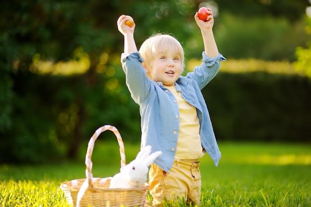 Caccia affascinante del ragazzino per l'uovo di pasqua nel parco di primavera il giorno di pasqua Foto Premium