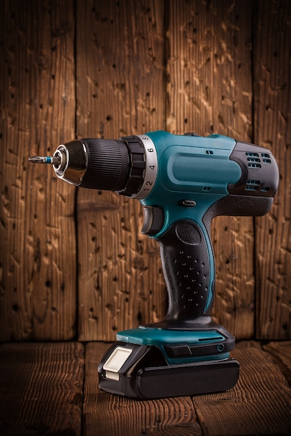 Cacciavite elettrico blu su fondo di legno rustico Foto Premium