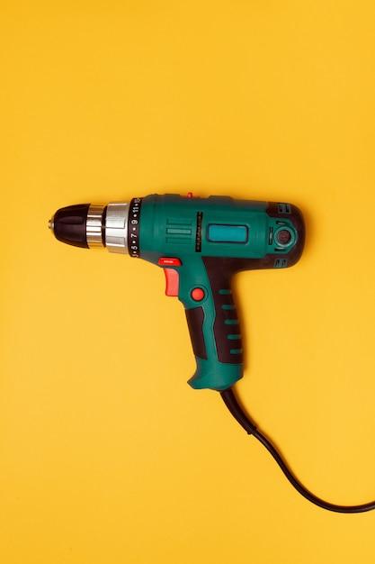 Cacciavite elettrico su uno sfondo giallo per lavori di costruzione Foto Premium