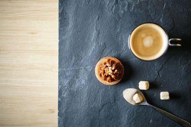 Caffè appena preparato sull'ardesia con mini pasticceria dello zucchero con lo spazio del testo Foto Premium