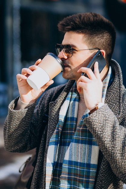 Caffè bevente del giovane uomo bello fuori e per mezzo del telefono Foto Gratuite