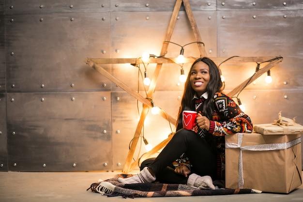 Caffè bevente della donna afroamericana su una notte di natale Foto Gratuite