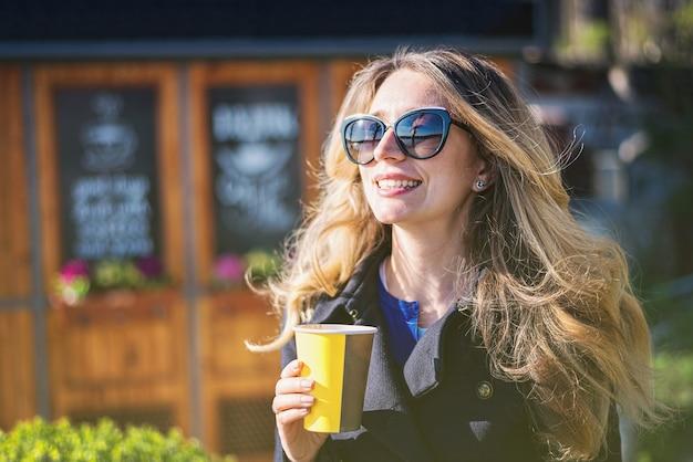 Caffè bevente della donna bionda caucasica felice Foto Premium