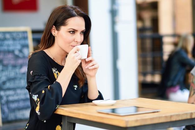 Caffè bevente della donna di mezza età in una barra di caffè urbana. Foto Premium
