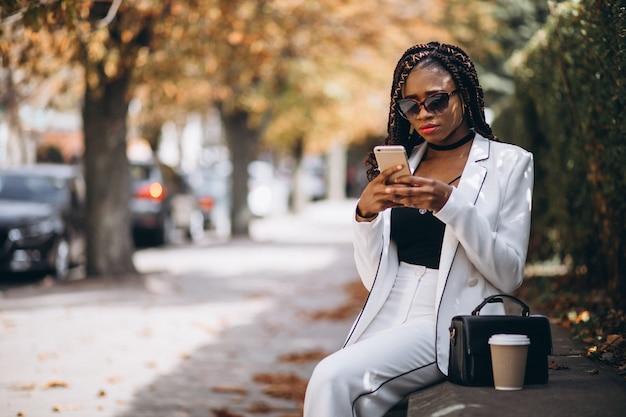 Caffè bevente della giovane donna africana e telefono usando Foto Gratuite