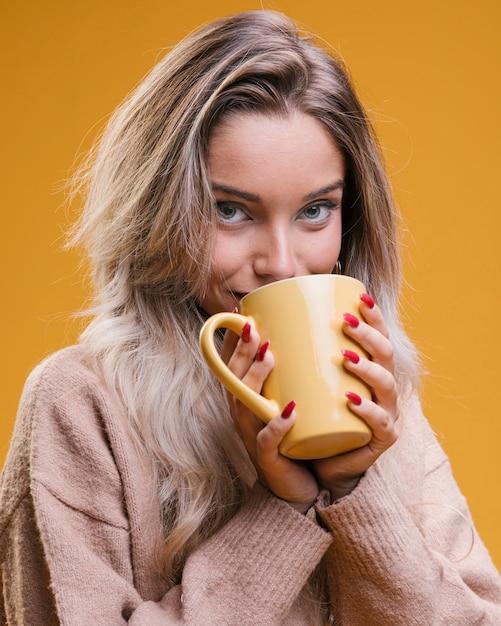 Caffè bevente della giovane donna contro fondo giallo Foto Gratuite