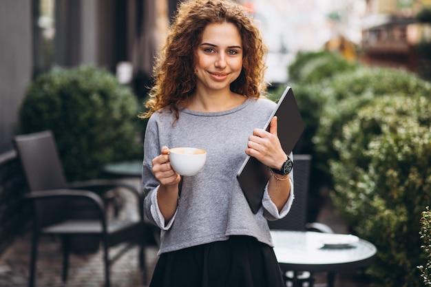 Caffè bevente della giovane donna di affari fuori del computer portatile della tenuta del caffè Foto Gratuite