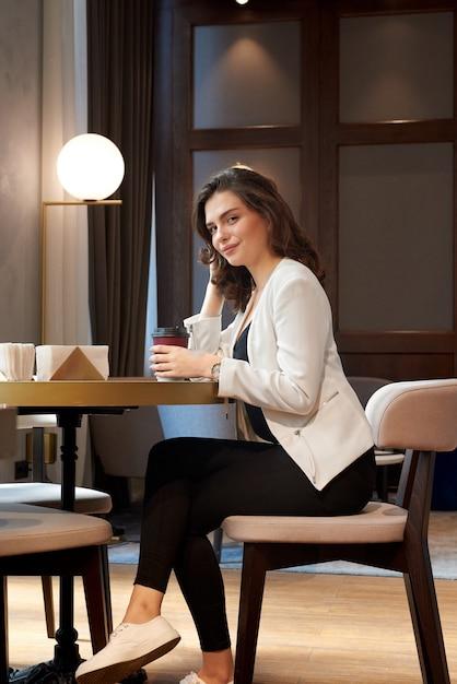 Caffè bevente della giovane ragazza sveglia in caffè Foto Premium