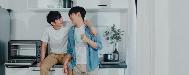Caffè bevente delle coppie gay asiatiche, divertendosi a casa. i giovani uomini lgbtq + che parlano felici si rilassano insieme riposano insieme il tempo romantico nella cucina moderna a casa la mattina. Foto Gratuite