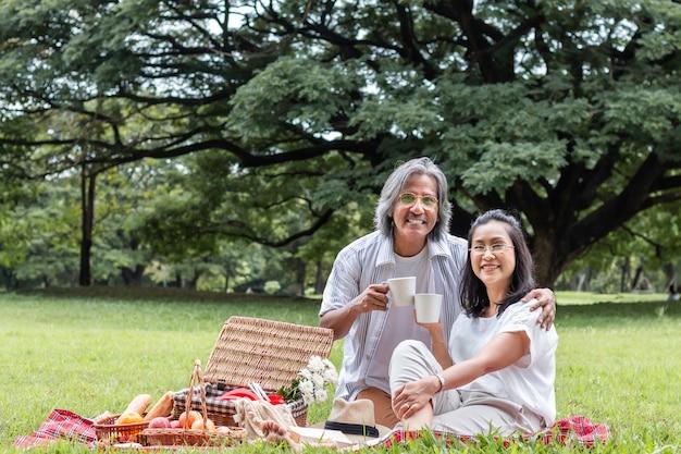 Caffè bevente e picnic delle coppie senior asiatiche al parco. Foto Premium
