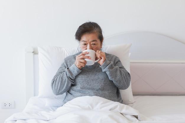 Caffè bevente o tè senior asiatico della donna anziana sul letto Foto Premium
