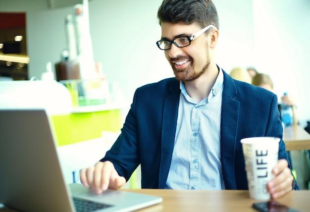 Caffè bevente sorridente dell'uomo dei pantaloni a vita bassa di giovane modo nel caffè della città durante l'ora di pranzo con il taccuino in vestito Foto Gratuite