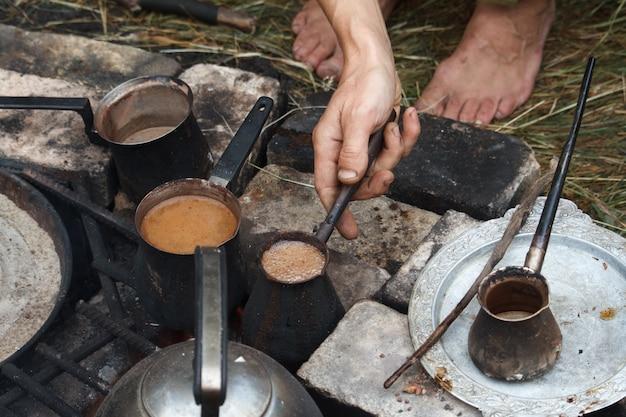 Caffè bollente in cezva turco su una griglia sopra un falò che brucia, un concetto di campeggio Foto Premium