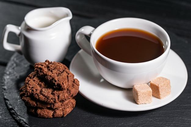Caffè con latte in una tazza bianca, servito con biscotti e zucchero Foto Premium