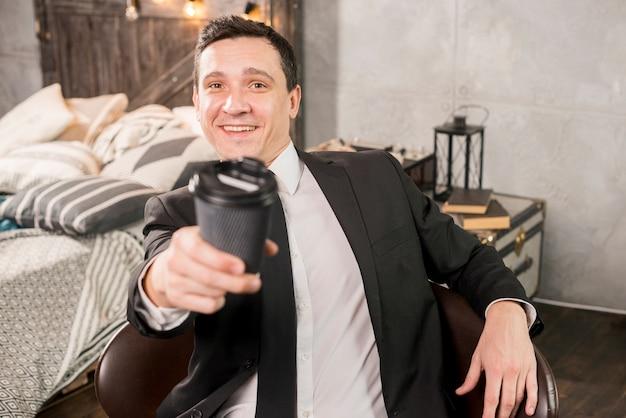 Caffè d'offerta maschio bello in tazza di carta Foto Gratuite