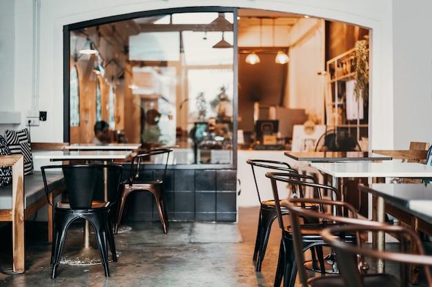 Caffè del bar decorato con colori caldi. lo rende caldo. adatto per riposare o sedersi. i mobili del negozio utilizzano sedie in ferro marrone. il piano del tavolo utilizza marmo bianco. sedile morbido e controllo del tono Foto Premium