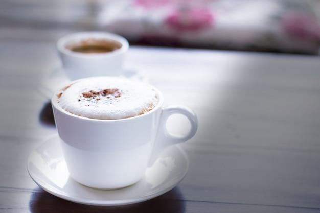 Caffè del cappuccino con guarnizione del cacao in tazza bianca in caffè con luce solare di mattina. Foto Premium