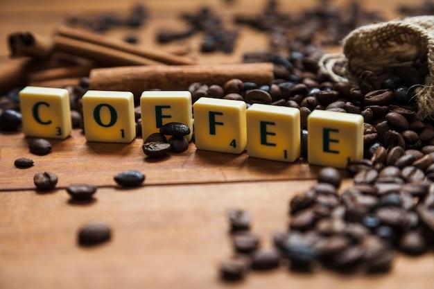 Caffè del primo piano che scrive vicino ai fagioli Foto Gratuite
