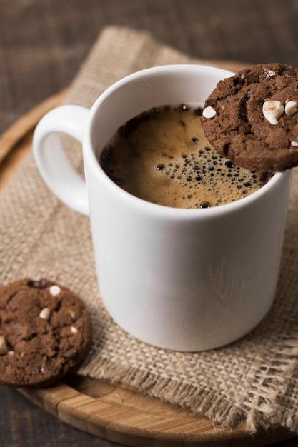 Caffè della prima colazione nell'alta vista bianca dei biscotti e della tazza Foto Gratuite