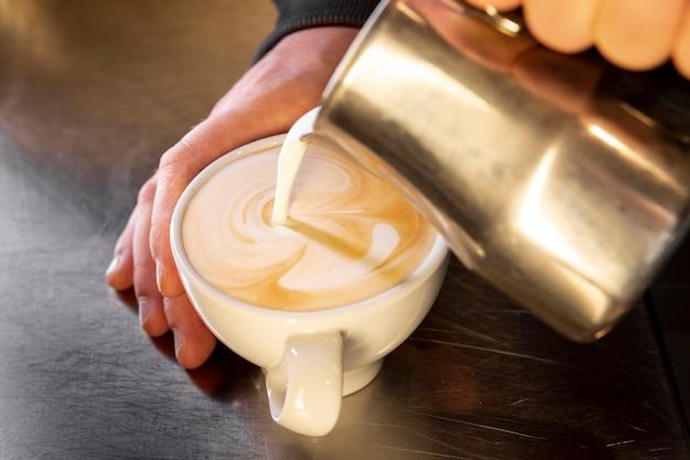 Caffè di versamento di barista del primo piano nella tazza Foto Gratuite