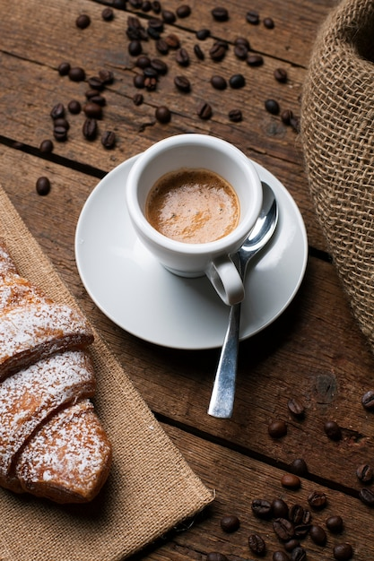 Caffè espresso con cornetto e semi di caffè Foto Gratuite