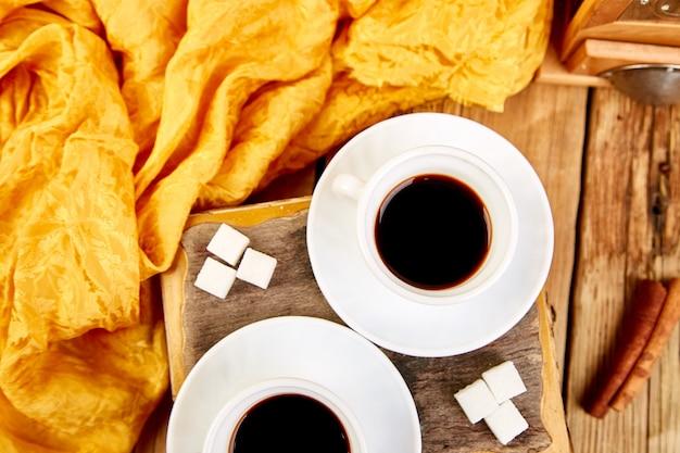 Caffè espresso di due tazze di caffè vicino al cubo dello zucchero Foto Premium