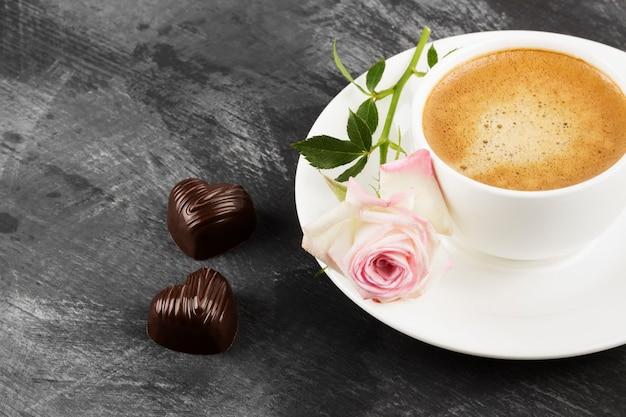 Caffè espresso in una tazza bianca, una rosa rosa e cioccolatini su uno sfondo scuro Foto Premium