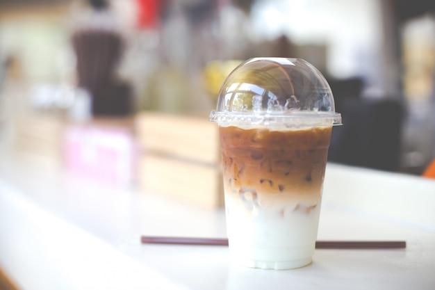 Caffè freddo in tazza di plastica su un tavolo di legno nella caffetteria Foto Premium