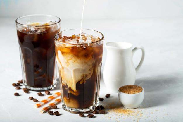 Caffè ghiacciato in un bicchiere alto con crema versata e caffè beato Foto Premium