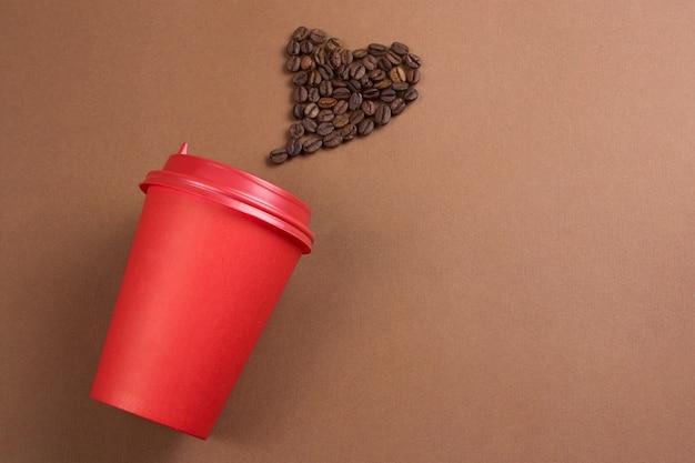 Caffè in carta per andare tazza e cuore fatto da chicchi di caffè Foto Premium