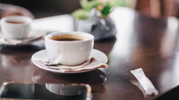 Caffè nero al mattino posto su un tavolo di legno e telefono. Foto Premium