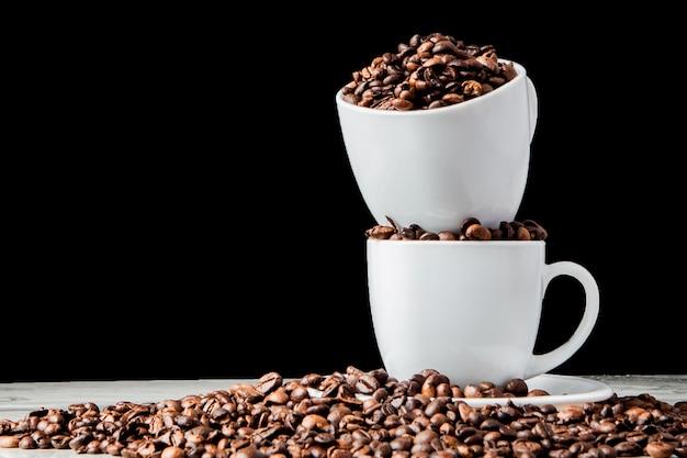Caffè nero in tazza bianca e chicchi di caffè su fondo nero. Foto Premium