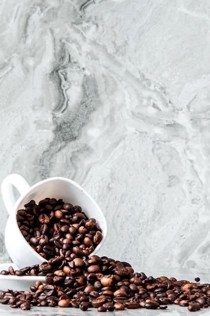 Caffè nero in tazza e chicchi di caffè su fondo di marmo. Foto Premium