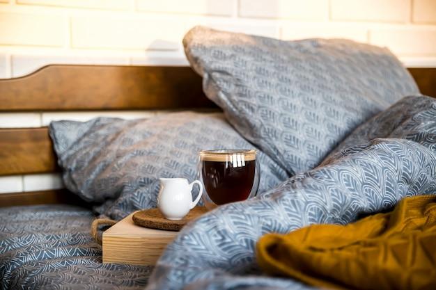 Caffè nero in una tazza trasparente a letto la mattina d'autunno Foto Premium