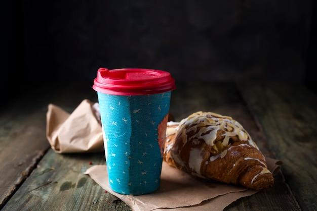 Caffè per andare in un bicchiere di carta con croissant Foto Premium