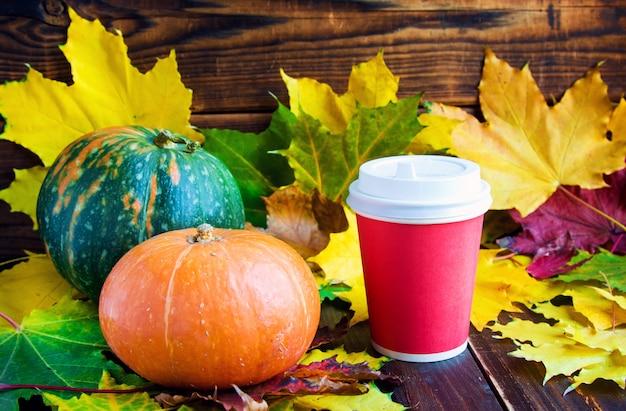 Caffè rosso per andare tazza con foglia e zucche di marmorea Foto Premium