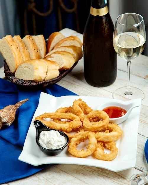 Calamari fritti serviti con maionese e salsa di peperoncino dolce, vino bianco e pane Foto Gratuite
