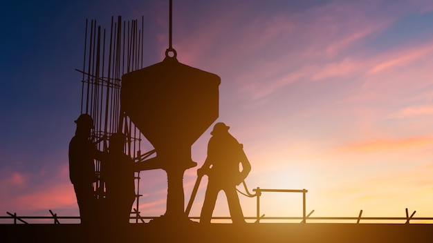 Calcestruzzo di versamento della costruzione del lavoratore delle squadre della siluetta. cantieri attraverso cantieri sfocati al tramonto Foto Premium