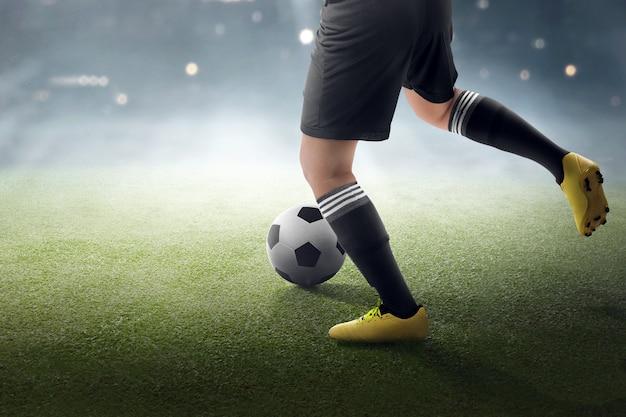 Calciatore che cerca di calciare la palla Foto Premium